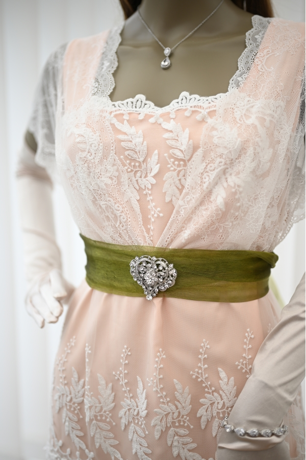 Close up of the top part of the lace dress with the green sash and broach