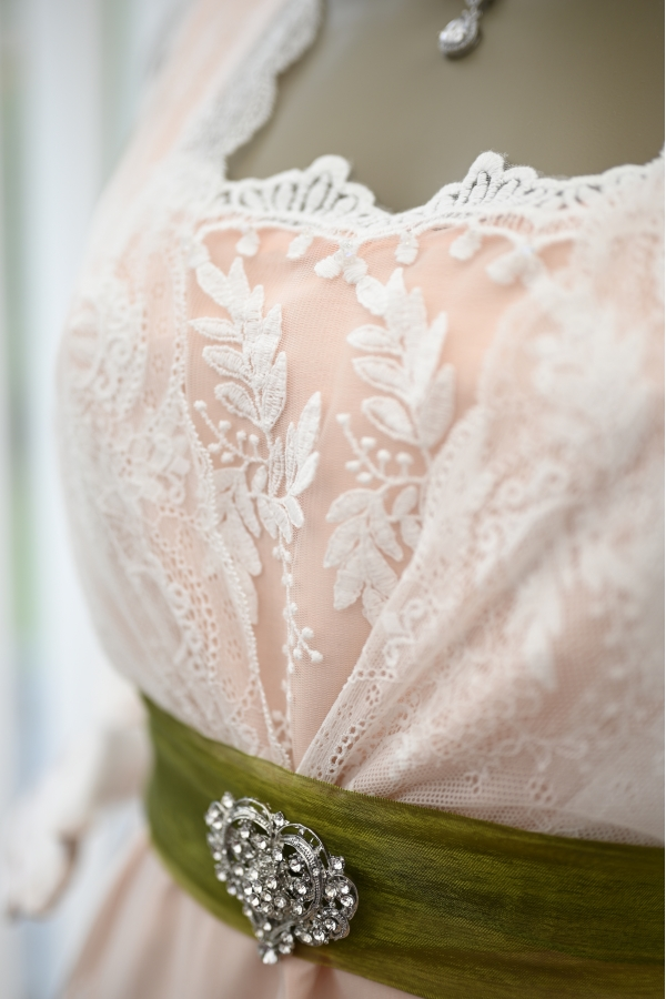 Close up of the lace bodice and the green sash with Edwardian brooch