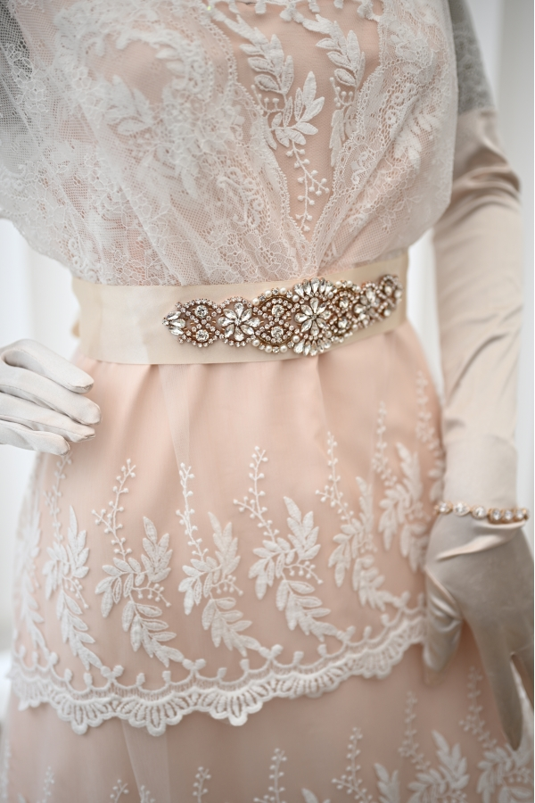 Close view of the blush beaded sash and the lace of the Titanic dress